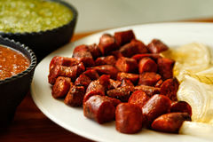 Sliced sausage with sauces. Sliced sausage on a white plate with sauces Royalty Free Stock Image
