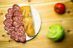 Sliced sausage on a white plate with bread on a wooden backgroun. D with tomato and lettuce royalty free stock photo