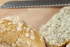 Sliced seeded wholegrain bread rolls laying on a breadboard Stock Images