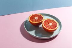 Sliced Sicilian orange on a blue plate. Creative concept of exotic fruits. royalty free stock images
