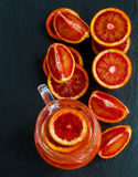 Sliced Sicilian red oranges and orange juice in glass jug on black stone background. Top view Royalty Free Stock Photo
