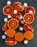Sliced Sicilian red oranges and orange juice in small glasses on black stone background. Top view stock photos