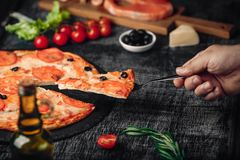 Sliced slice of pizza in hand with cheese, trout, tomatoes, olives and shrimps on chalk board. Sliced slice of pizza in hand with cheese, trout, tomatoes cherry stock photo