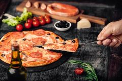 Sliced slice of pizza in hand with cheese, trout, tomatoes, olives and shrimps on chalk board. Sliced slice of pizza in hand with cheese, trout, tomatoes cherry stock image