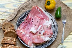 Pieces of Italian prosciutto on a plate. Sliced slices of Italian prosciutto, bread and peppers on a plate close-up on a wooden table Royalty Free Stock Image