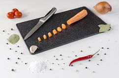 Sliced into small pieces carrot on a dark cutting board stock image