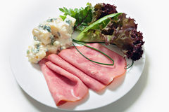 Sliced smoked beef and salad. Slices of smoked beef ham served with potato salad and garden fresh vegetables royalty free stock image