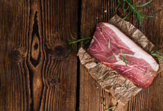 Sliced Smoked Ham. With some fresh herbs on rustic wooden background Royalty Free Stock Photo