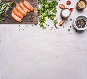 Sliced smoked salmon on a cutting board with parsley, cherry tomatoes, rosemary and pepper border ,place text  on wooden rusti Stock Photo