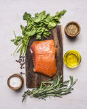 Sliced smoked salmon with parsley and rosemary, oil and spices on a cutting board wooden rustic background top view Royalty Free Stock Photos