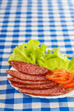 Sliced ​​smoked sausage, tomatoes, lettuce Royalty Free Stock Photo