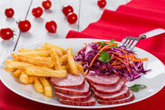 Sliced smoked veal fillet, french fries and red cabbage salad with carrots cut into strips and parsley dressing with vinegar and stock photos
