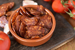 Sliced spanish chorizo. Closeup of an earthenware bowl with some slices of Spanish chorizo, a pork sausage typical of Spain, on a rustic wooden table with some Royalty Free Stock Image