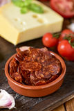 Sliced spanish chorizo, garlic, tomato and cheese. Closeup of an earthenware bowl with some slices of Spanish chorizo, a pork sausage typical of Spain, on a Stock Images