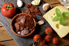 Sliced spanish chorizo, garlic, tomato and cheese. High-angle shot of an earthenware bowl with some slices of Spanish chorizo, a pork sausage typical of Spain Royalty Free Stock Images
