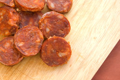 Sliced spanish chorizo sausage on rustic board Royalty Free Stock Images