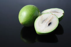 Sliced Starapple. Two pieces of starapple, one sliced, placed on reflective table Royalty Free Stock Photo