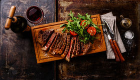 Sliced steak with arugula salad and Red wine. Sliced grilled beef barbecue Striploin steak with arugula salad and Red wine on dark background Royalty Free Stock Images