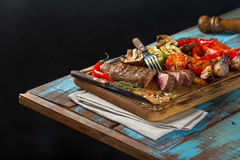 Sliced steak grill with grilled vegetables on the wooden table. With a fork and a knife Stock Image