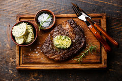 Sliced steak Ribeye with herb butter. Sliced grilled steak Ribeye with herb butter on cutting board on wooden background Stock Photo