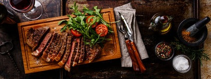 Sliced steak and salad. Sliced grilled beef barbecue Striploin steak and salad with tomatoes and arugula on cutting board on dark background royalty free stock photos