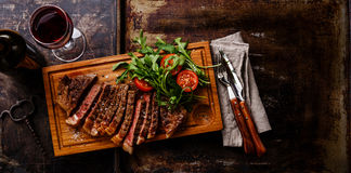 Sliced steak and salad. Sliced grilled beef barbecue Striploin steak and salad with tomatoes and arugula on cutting board on dark background copy space Royalty Free Stock Photo