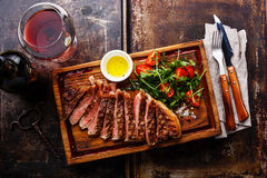 Sliced steak with salad and wine. Sliced grilled beef barbecue Striploin steak and salad with tomatoes and arugula on cutting board and wine on dark background Royalty Free Stock Image