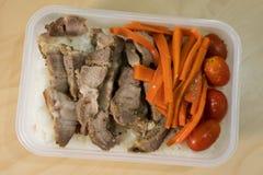 Sliced stekte griskött som tjänades som med morötter och tomater på ris royaltyfria bilder