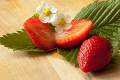 Sliced strawberries on a leaf with flower. Sliced strawberries with leaves and flowers Royalty Free Stock Images