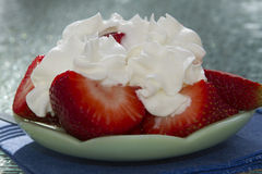 Sliced Strawberries with Whipped Cream. On a decorative green plate.  They are served outdoors on a glass table Stock Photo