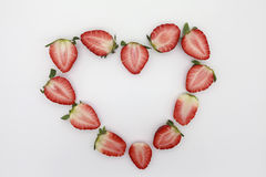 Sliced strawberries on white background. Sliced strawberries in heart shape on white background.Space in the center can be used for greeting text Royalty Free Stock Image