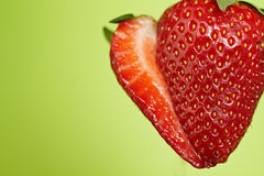 Sliced strawberry on green background Stock Photos