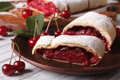 Sliced strudel with cherry close-up on a plate. horizontal Stock Photos