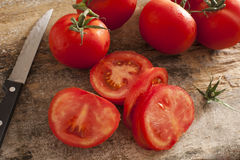 Sliced succulent red tomatoes beside serrated knife Royalty Free Stock Photo