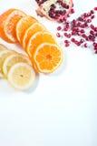 Sliced tangerine, lemon and pomegranate over the white background Stock Photos