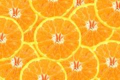 Sliced tangerine orange stacked to create fruit background. Royalty Free Stock Photos