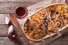 Sliced  Tarte flambee and red wine close-up. horizontal top view Stock Photos