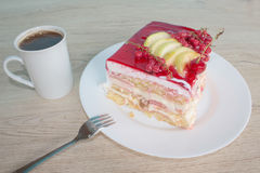 Sliced tasty cake and coffee on wooden table. Cake with fresh red currant on the plate Stock Photos