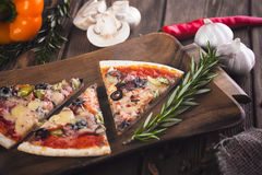 Sliced tasty fresh pizza with mushrooms and sausage on a wooden background. Stock Photography