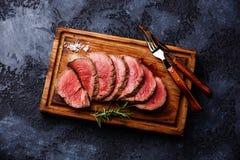 Sliced tenderloin Steak roastbeef. Sliced grilled tenderloin Steak roastbeef on wooden cutting board on dark background stock photography