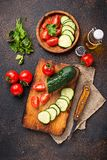 Sliced tomato and cucumber on cutting board. Top view Royalty Free Stock Image