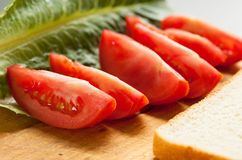 Sliced tomato with green salad and bread on the wooden tray. Sel Royalty Free Stock Image