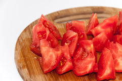 Sliced tomato for salad on the kitchen cutting board Stock Image