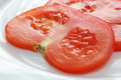 Sliced tomato on white plate. Extreme close up Stock Images