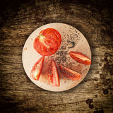Sliced tomato on wooden plate Stock Photos
