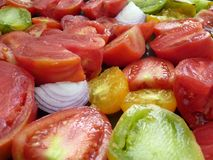 Sliced tomatoes. In the colours green, red, yellow and in different sizes, together with some onion slices to prepare a tomatosoup royalty free stock photos