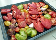 Sliced tomatoes on baking tray. Sliced tomatoes in all kinds of varieties, like red, yellow, green, black and in divers sizes, on a baking tray royalty free stock photography