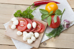 Sliced tomatoes, basil and mozzarella cheese on a wooden board stock photos