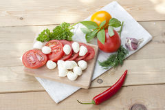 Sliced tomatoes, basil and mozzarella cheese on a wooden board. Selective focus Royalty Free Stock Images