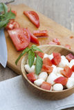 Sliced tomatoes, basil and mozzarella cheese on a wooden plate. Selective focus Stock Photos